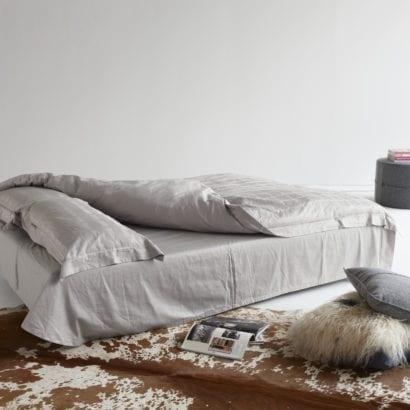 grey bed, rug and ottoman