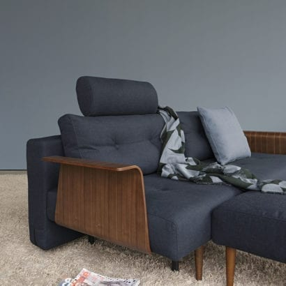 blue sofa bed with wooden arms on carpet