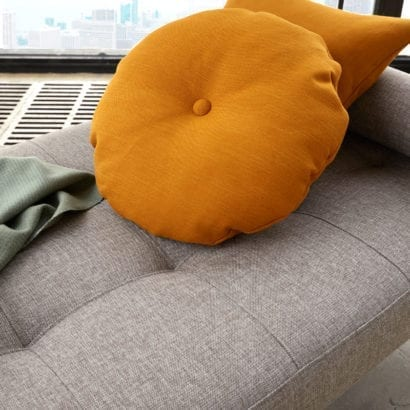 grey daybed with orange cushions